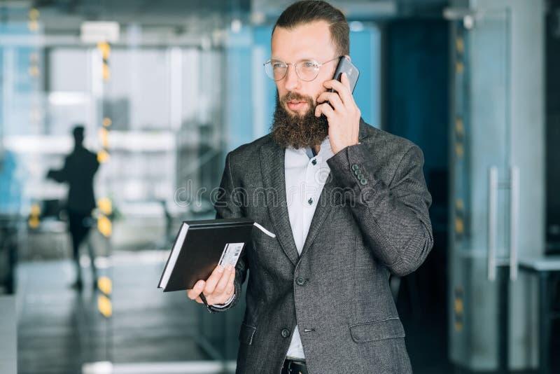 Il telefono di conversazione dell'uomo di affari pensa il richiamo di proposito immagine stock
