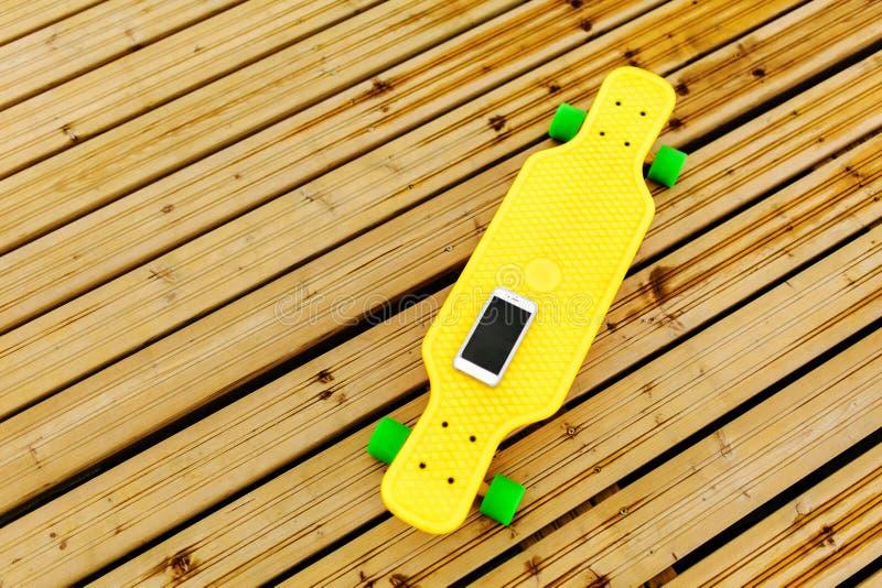 Il telefono si trova su un longboard di plastica giallo, che è situato sulla pavimentazione di legno Vista superiore fotografia stock libera da diritti