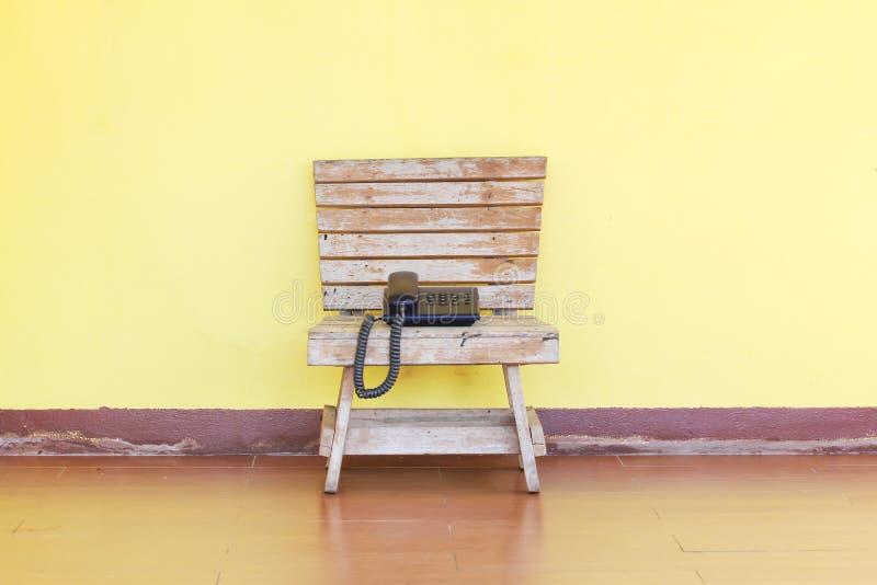 Il telefono sta su una sedia di legno immagini stock