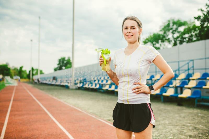 Il tema è sport e salute La bella giovane donna caucasica con il grande corridore dell'atleta dei seni sta riposante sul funziona immagine stock
