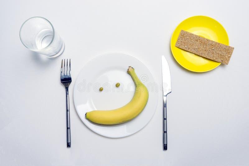 Il tema di cibo sano: una banana e piselli sotto forma di sorriso su un piatto, accanto ad un coltello e ad una forcella su una t fotografie stock libere da diritti