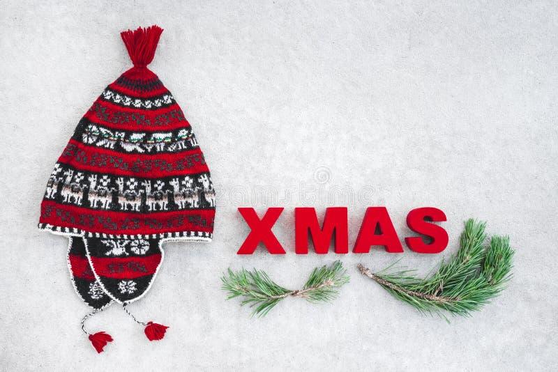 Il tema di natale con il cappello ed il pino rossi dell'inverno si ramifica fotografia stock