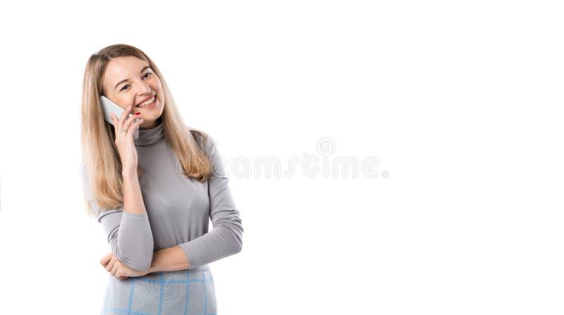Il tema di una donna di affari e delle conversazioni telefoniche La bella giovane donna caucasica utilizza un microtelefono dello immagine stock