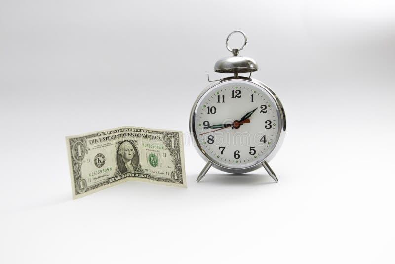 Il tempo è denaro Una condizione della banconota in dollari accanto ad un grande orologio fotografie stock libere da diritti