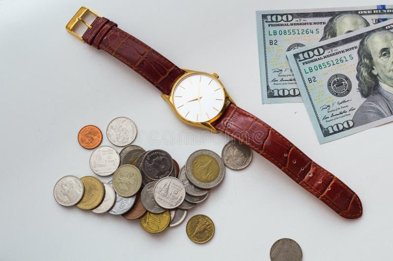 Il tempo ? denaro Orologio con le banconote in dollari e le monete su un fondo bianco immagine stock libera da diritti