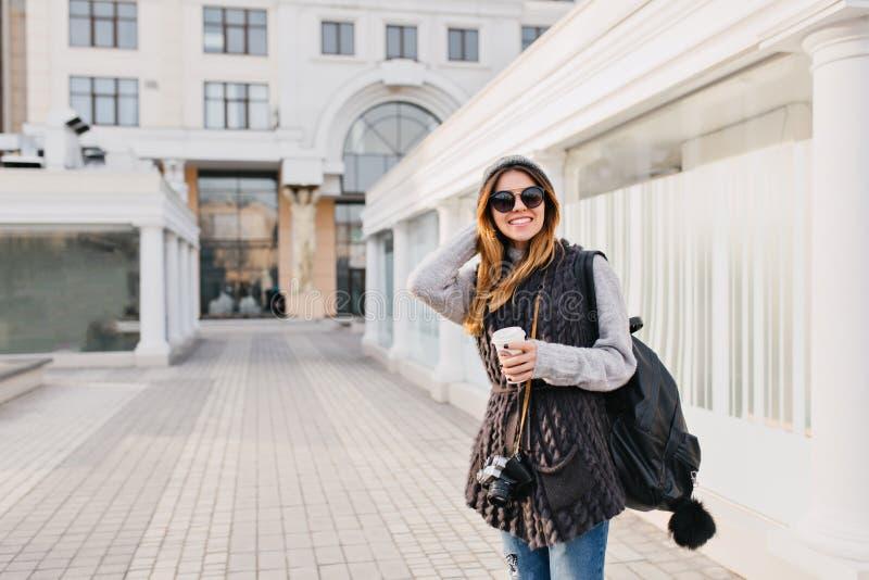 Il tempo felice di viaggio nel centro urbano moderno della giovane donna graziosa yoyful in occhiali da sole, maglione di lana de fotografia stock