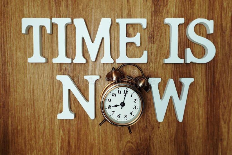 Il tempo ora ? lettera dell'alfabeto con la sveglia su fondo di legno fotografie stock
