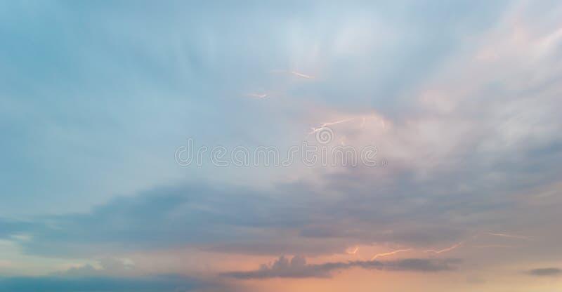 Il temporale luminoso del fulmine bianco sulle nuvole blu rosa porpora del cielo di sera abbellisce fotografie stock libere da diritti