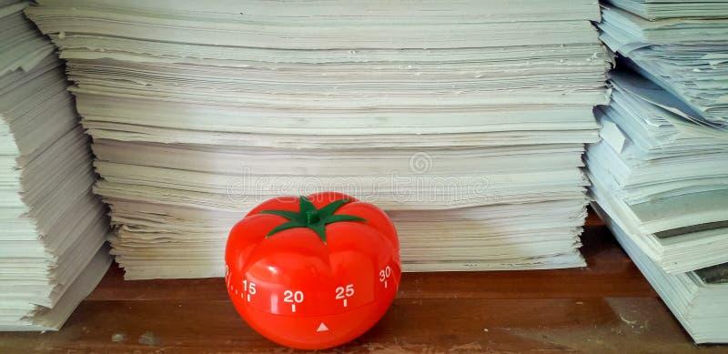 Il temporizzatore di Pomodoro nel fondo delle strutture di carta ha accatastato immagine stock libera da diritti