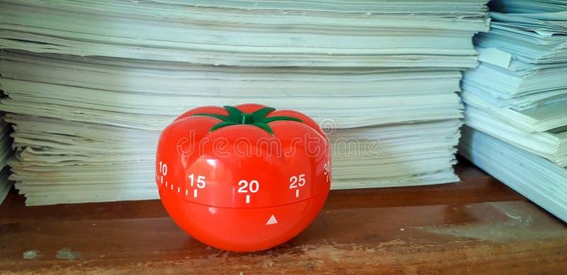 Il temporizzatore di Pomodoro nel fondo delle strutture di carta ha accatastato fotografia stock