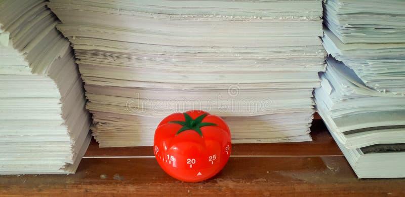 Il temporizzatore di Pomodoro nel fondo delle strutture di carta ha accatastato fotografie stock