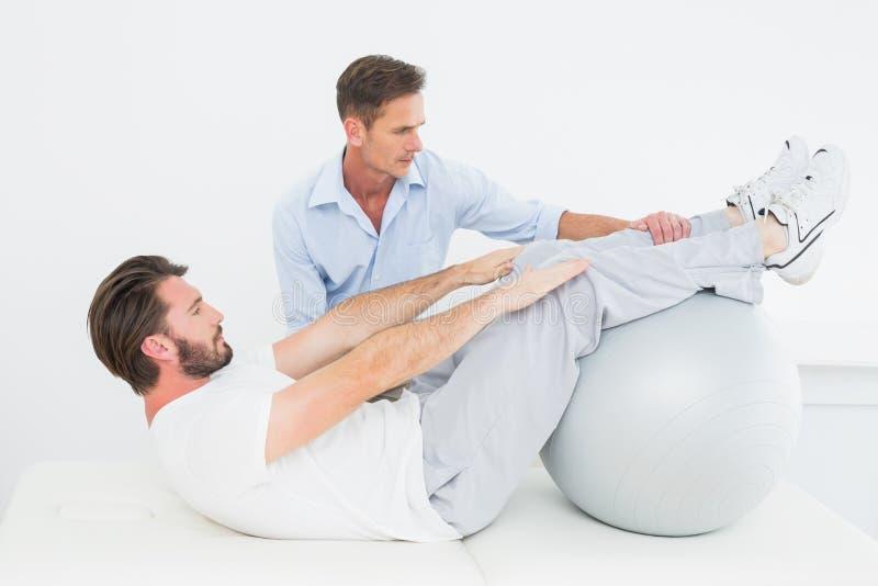 Il terapista fisico che assiste il giovane si siede aumenta fotografia stock