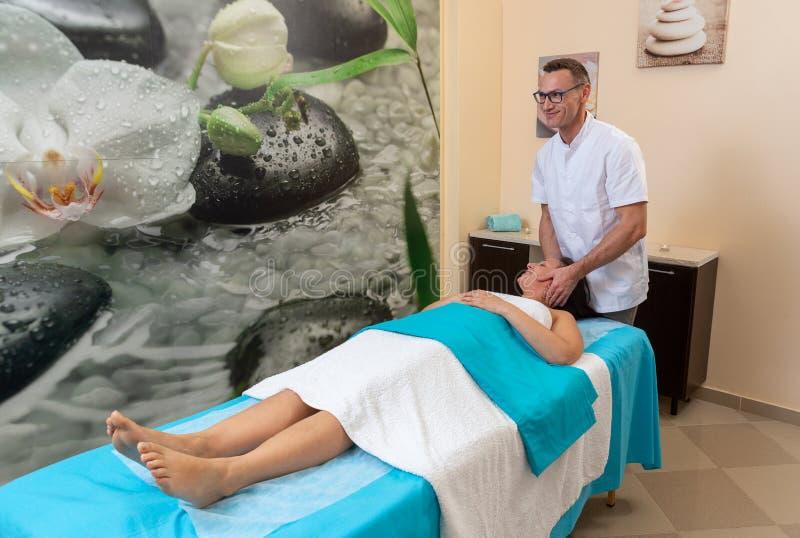 Il terapista maschio dell'osteologo massaggia il collo del paziente, dopo la lesione immagine stock libera da diritti