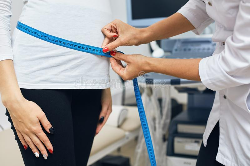 Il terapista sta misurando uno stomack di una donna che porta un bambino fotografie stock