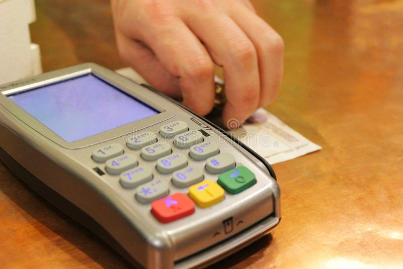 Il terminale POS di credito e la mano di un uomo mette i contanti fotografia stock libera da diritti