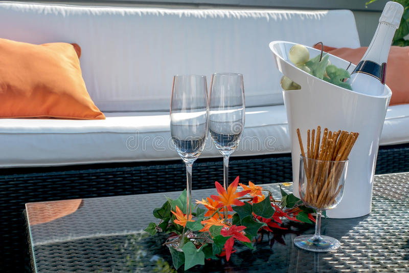 Il terrazzo con i vetri del champagne ed il champagne imbottigliano il dispositivo di raffreddamento fotografia stock libera da diritti