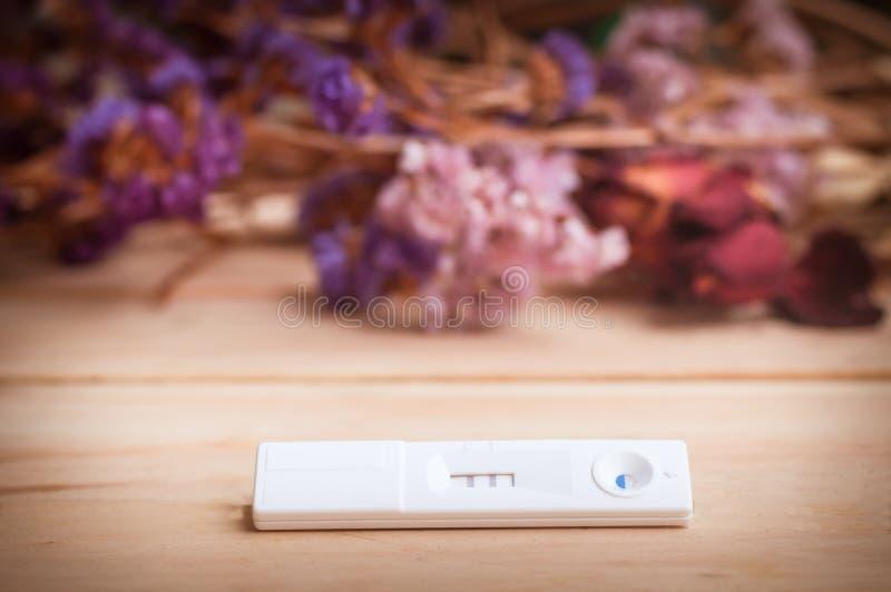 il test di gravidanza ed i fiori secchi su fondo di legno proce fotografie stock libere da diritti