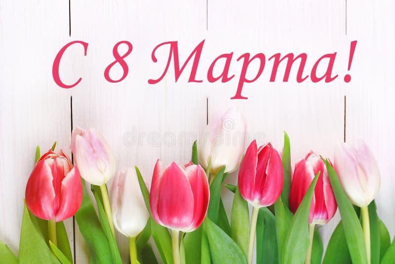 Il testo nel Russo: dall'8 marzo Giorno internazionale del ` s delle donne Tulipani su una tavola di legno bianca immagine stock