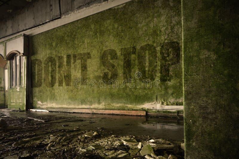 Il testo non si ferma sulla parete sporca in una casa rovinata abbandonata fotografia stock