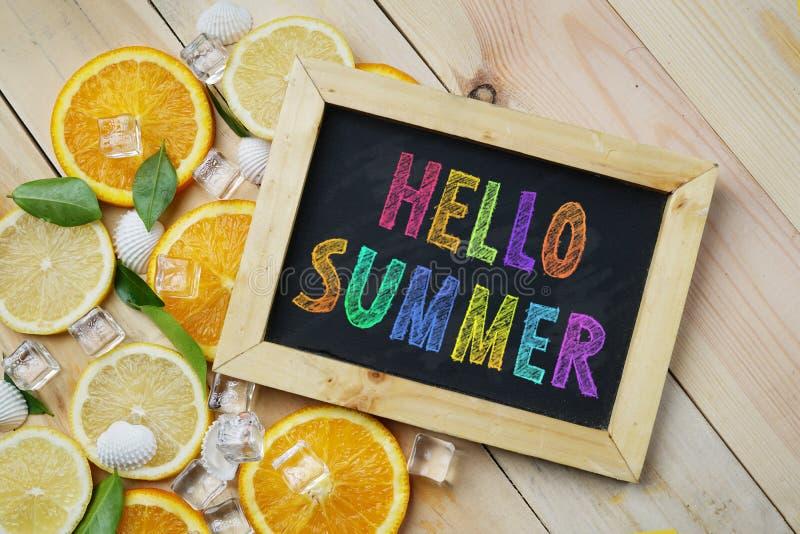 Il testo variopinto dell'estate di ciao sull'arancia della lavagna lascia il ghiaccio del cubo fotografia stock