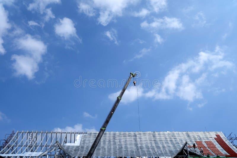 Il tetto in costruzione con la gru gigante ed i lavoratori stanno funzionando immagine stock libera da diritti