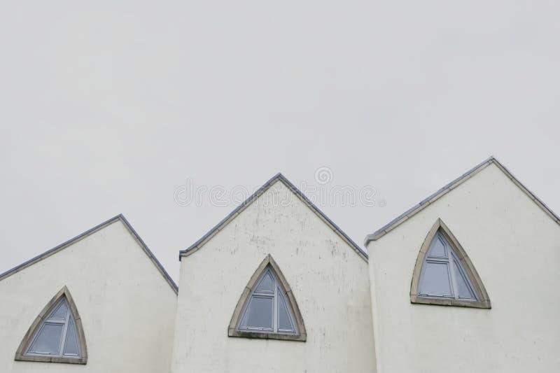 Il tetto della chiesa ed il triangolo delle finestre modellano in tre e soppressione il cielo vuoto immagine stock libera da diritti