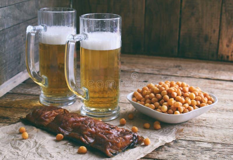 Il tifoso ha messo con le tazze della birra, della bottiglia e degli spuntini salati su fondo di legno Alimenti industriali per b fotografia stock
