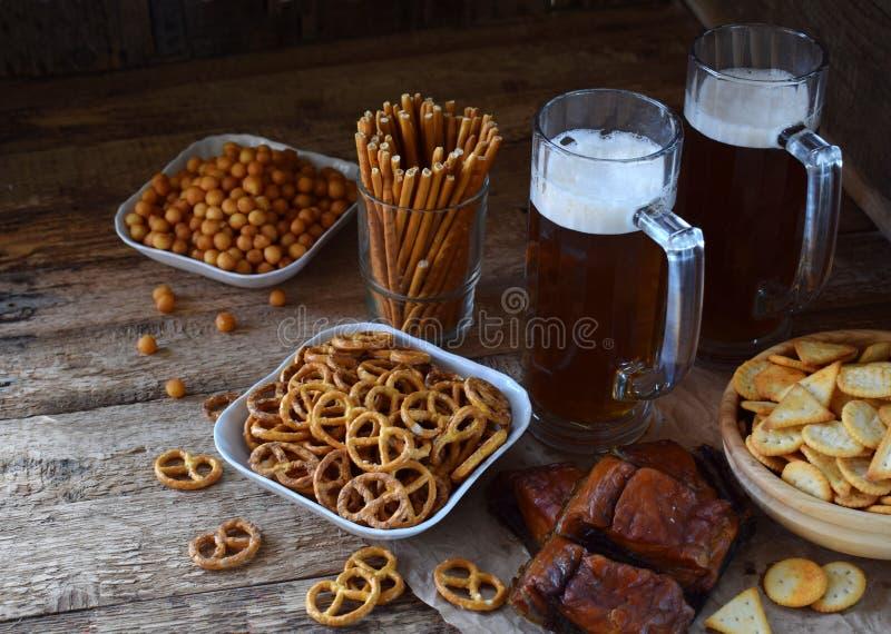 Il tifoso ha messo con le tazze della birra, della bottiglia e degli spuntini salati su fondo di legno Alimenti industriali per b fotografia stock libera da diritti