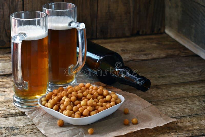 Il tifoso ha messo con le tazze della birra, della bottiglia e degli spuntini salati su fondo di legno Alimenti industriali per b immagini stock