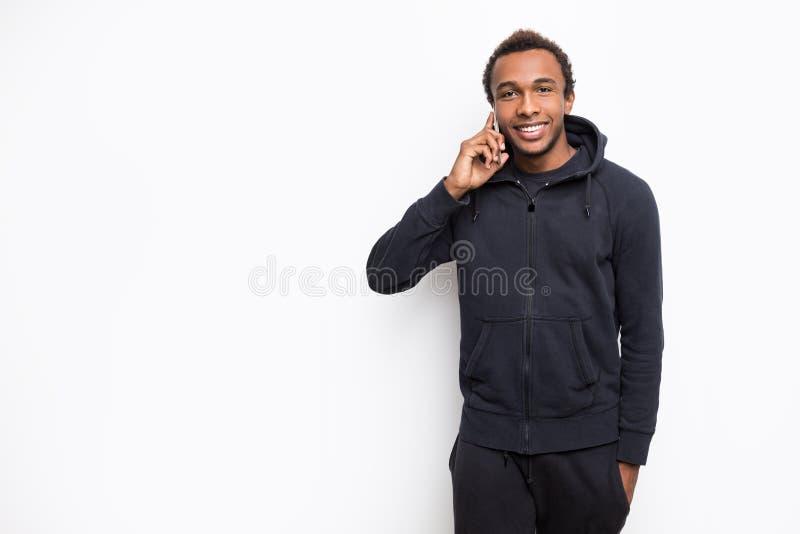 Il tipo africano sorridente sta parlando con suo amico sul telefono fotografia stock