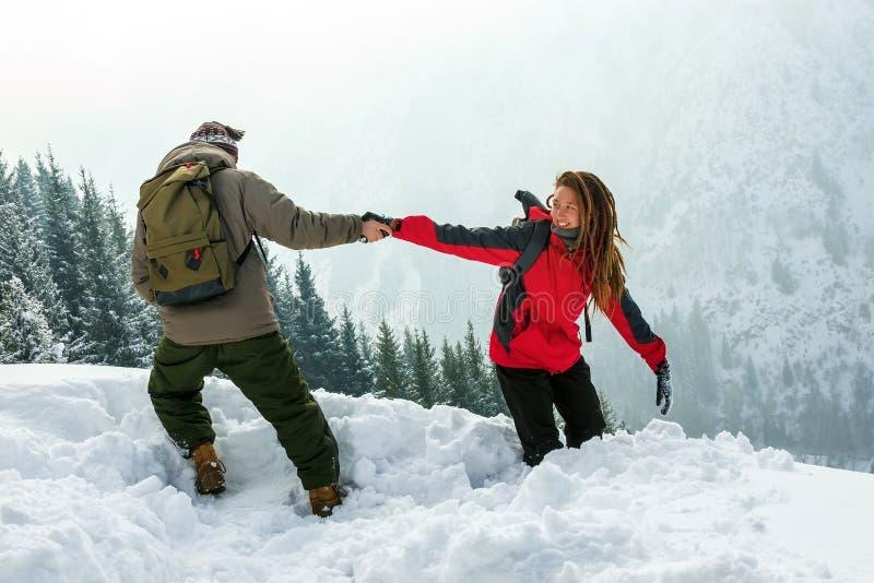 Il tipo aiuta la ragazza ad uscire della neve profonda Viaggio di inverno fotografie stock