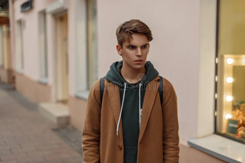 Il tipo alla moda alla moda in un cappotto d'annata con una maglia con cappuccio cammina fotografie stock libere da diritti
