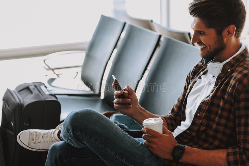 Il tipo allegro sta godendo del telefono e del caffè all'aeroporto fotografia stock