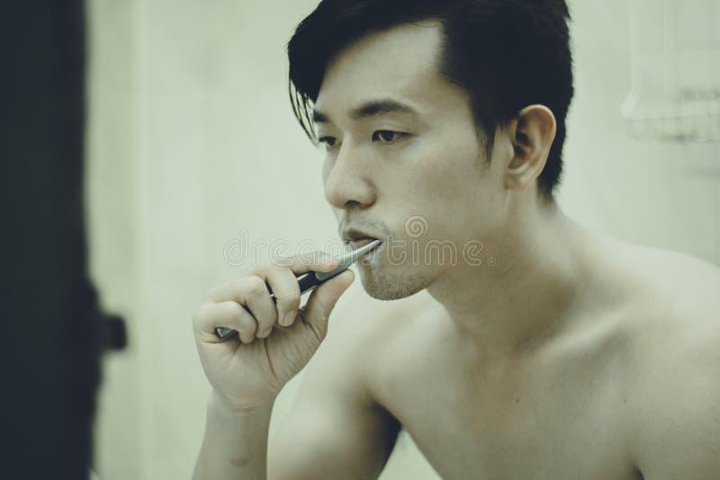 Il tipo asiatico pulisce i suoi denti immagini stock libere da diritti