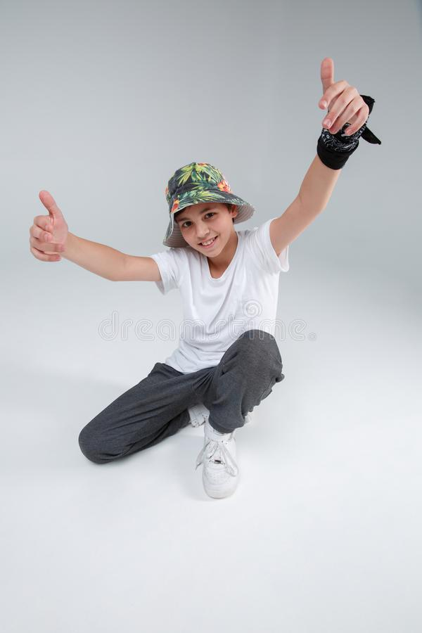 Il tipo attivo è un adolescente, occupante ed attivamente alzandosi le sue mani sopra la sua si dirigono su un fondo grigio fotografie stock