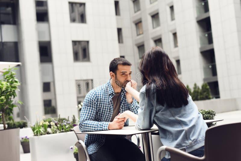 Il tipo bacia la mano della ragazza che si siede alla tavola in un caffè fotografia stock libera da diritti