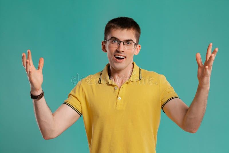 Il tipo bello in una maglietta casuale gialla sta posando sopra un fondo blu fotografia stock libera da diritti