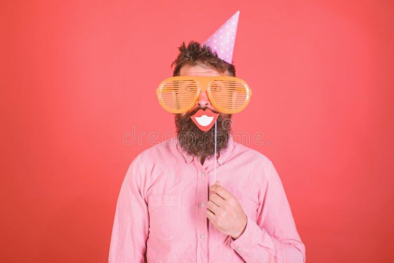 Il tipo in cappello del partito celebra, posando con i puntelli della foto Pantaloni a vita bassa in occhiali da sole giganti che fotografia stock