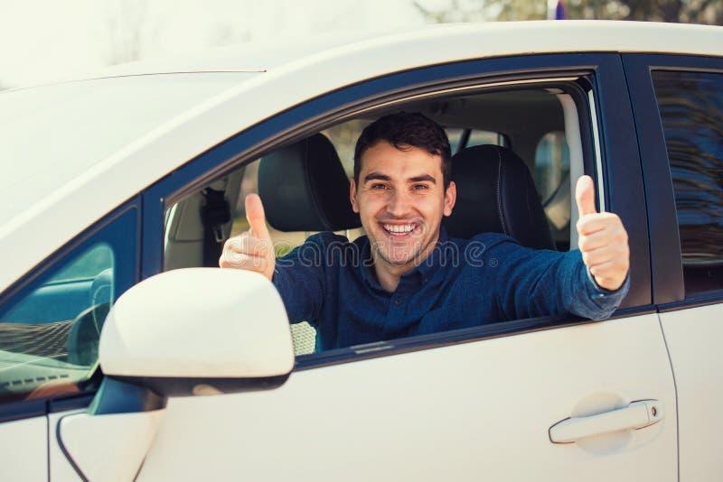 Il tipo casuale eccitato che si siede dietro il volante dell'automobile che mostra i pollici sul gesto così ha passato l'esame ed fotografia stock
