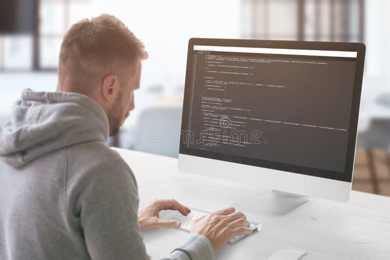 Il tipo che programma su un computer nell'ufficio fotografia stock