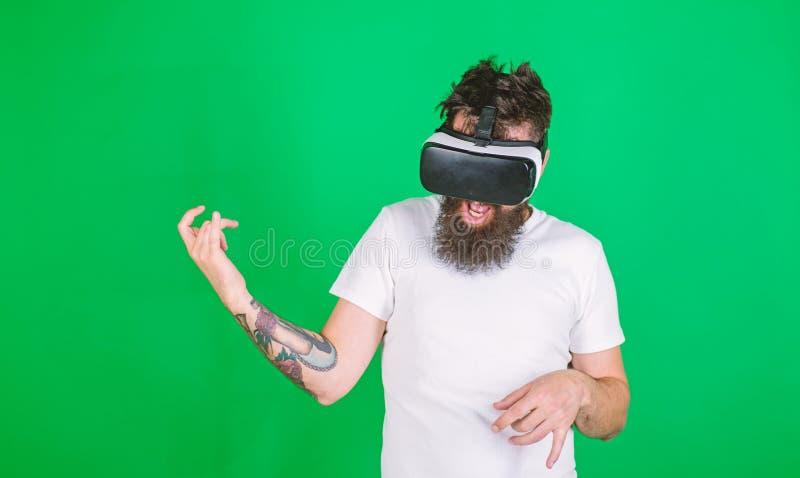 Il tipo con i vetri di VR impara giocare la musica sulla chitarra Chitarrista dei pantaloni a vita bassa su tecnologia moderna di immagine stock libera da diritti