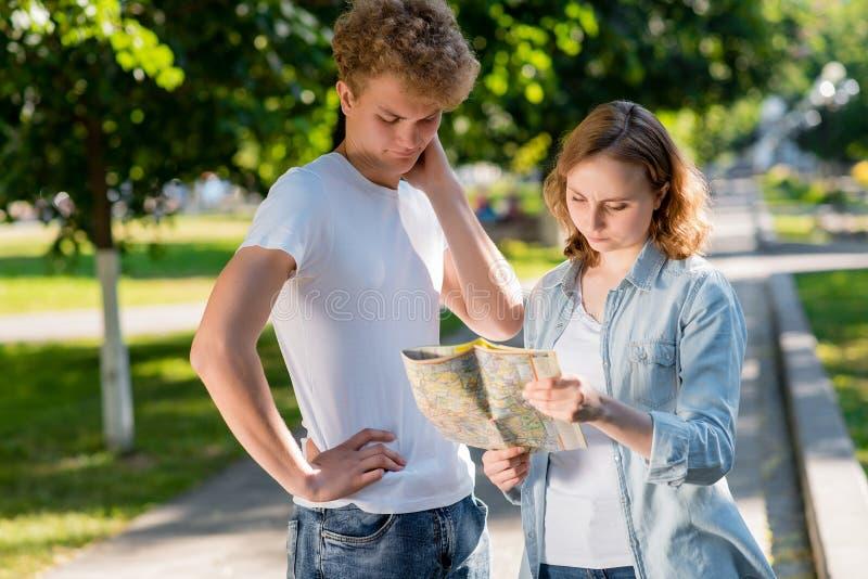 Il tipo con la ragazza sulla natura di estate in città In sue mani tiene un programma di strada Hanno perso il loro modo e non co fotografia stock