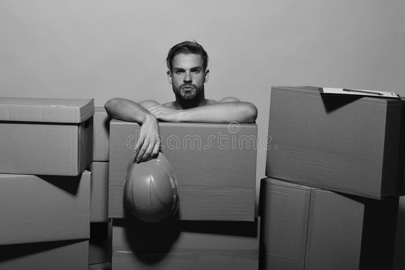 Il tipo con le mani pulite si siede dietro le scatole, spazio della copia Sessualità e concetto commovente Macho con il fronte se fotografia stock