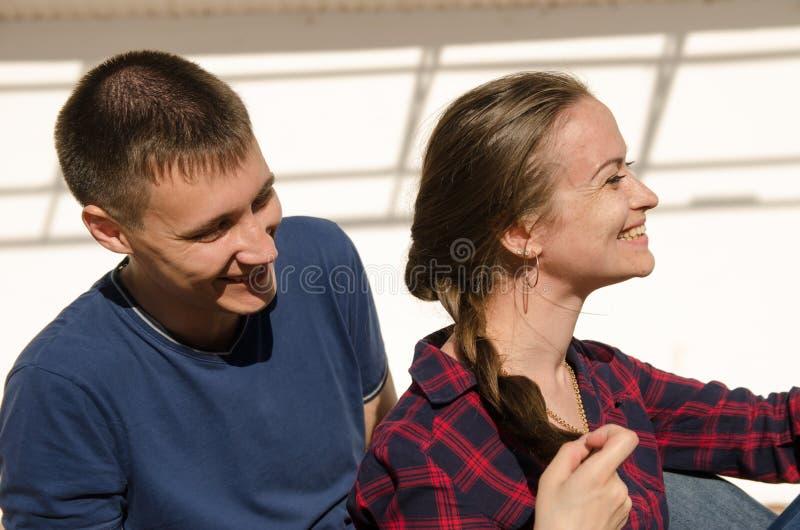 Il tipo con un breve taglio di capelli esamina una ragazza con capelli scuri lunghi e una camicia di plaid immagini stock libere da diritti