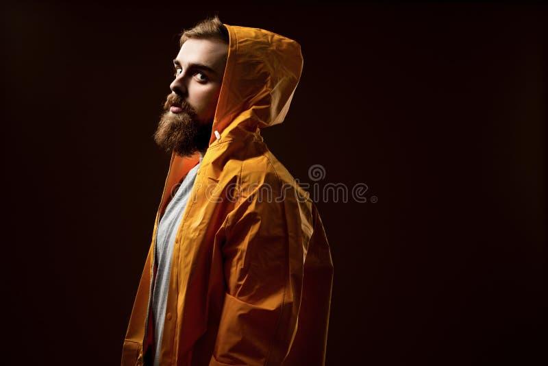 Il tipo con una barba ed i baffi vestiti in una maglietta grigia ed in un rivestimento giallo con un cappuccio sta stando su un f fotografia stock libera da diritti