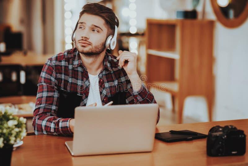 Il tipo in cuffie lavora a distanza sul computer portatile all'interno fotografie stock