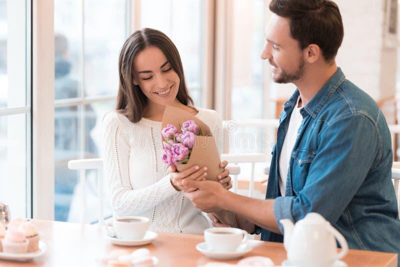 Il tipo dà i fiori alla ragazza nel caffè fotografie stock libere da diritti