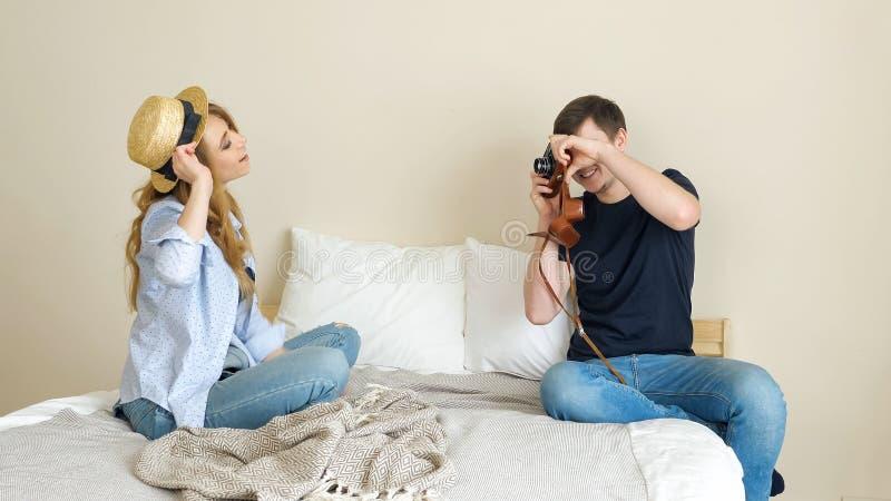 Il tipo della ragazza prende le immagini con la vecchia macchina fotografica che posa in cappello di giocatore di bocce fotografia stock
