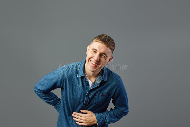 Il tipo di risata vestito in una camicia dei jeans tiene la sua mano sullo stomaco nello studio sui precedenti grigi immagine stock libera da diritti