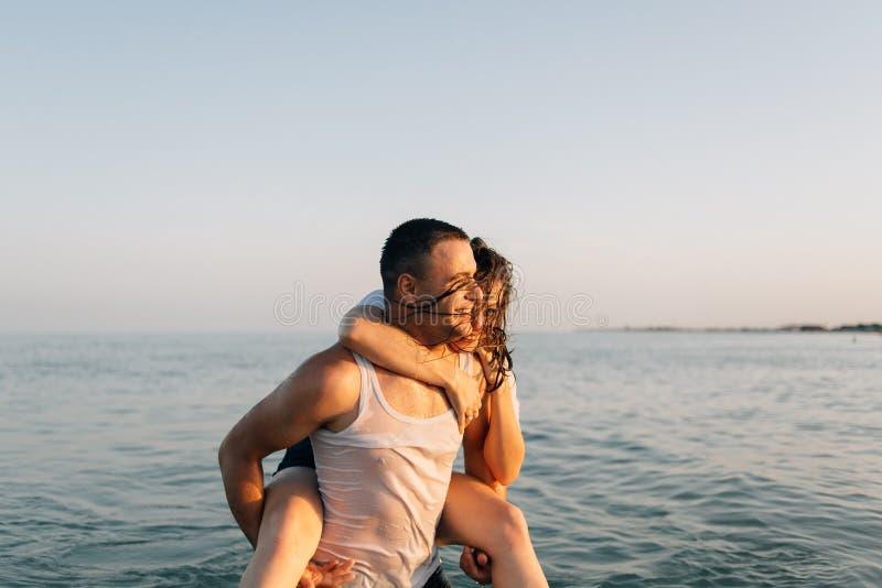 Il tipo e la ragazza con un sorriso sono nel mare immagine stock